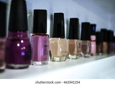 Purple, pink, and tan nail polish on a white shelf.