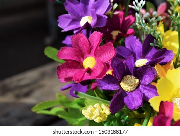 Purple, pink and yellow fake flowers in sunshine