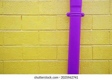 Purple pipes on yellow brick wall. Picturesque background of the colourful house.