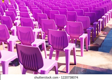 Purple plastic chairs on the floor.
