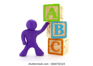 Purple plasticine character and wooden cubes. Alphabet blocks. Isolated on white background