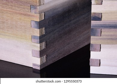 Purple poplar wood finger joints on dark surface with copy space.