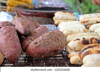 Purple potatos and bananas are grilling on stove. Famous asian street food especially in cool day.