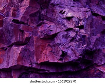Purple red orange grunge background. Toned mountain texture. Rough rock texture in neon light.    Fantasy, science fiction, surreal.