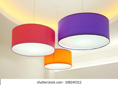 Purple, red and orange round stylish lampshades hang from ceiling