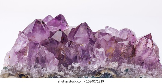 Purple rough Amethyst quartz crystals geode on white background.
