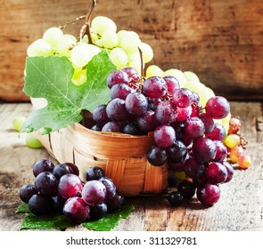 Purple round ripe grapes in a wicker basket on an old wooden background, selective focus