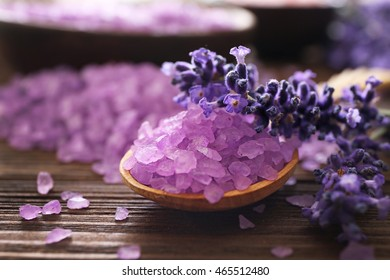 Purple sea salt with lavender on wooden background