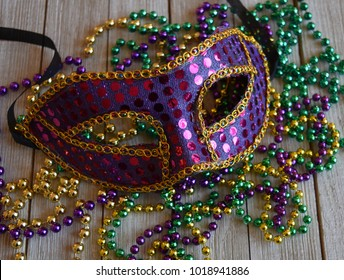 Purple sequin Mari Gras Mask with beads on a wood background