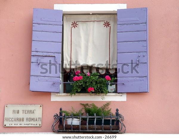 Purple shutters on a pink wall