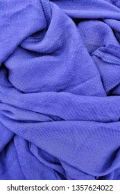 Purple silk fabric is laid out waves wrinkled for background or texture