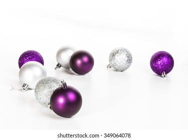 purple and silver Christmas balls on a white table