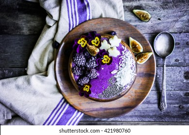 Purple smoothie bowl on wooden background