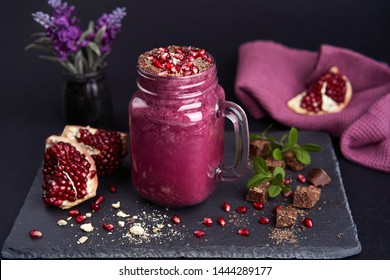 Purple Smoothie made of Pomegranate on a black stone plate over dark background