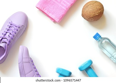 Purple sneakers, pink towel, coconut, blue dumbbells and mineral water bottle. Fitness mockup. Gym, healthy lifestyle flat lay photography