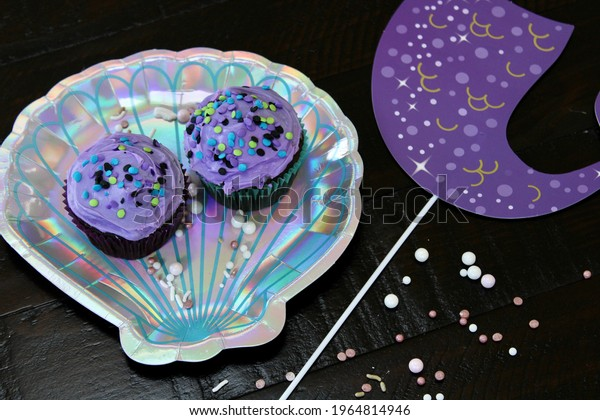 A purple, sparkly mermaid tail on a stick with two cupcakes smothered with purple frosting and confetti sprinkles on a metallic clam shell plate with shiny pearls scattered around.