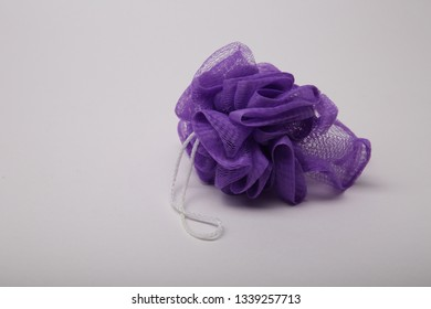 purple sponge with a loop for the body.   purple washcloth isolated on white background.
