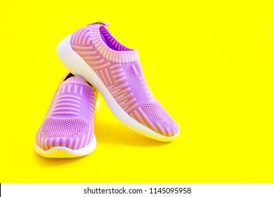 purple sport shoes on a yellow background