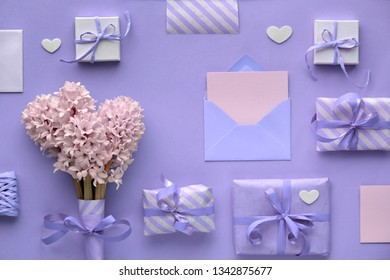 Purple springtime  background with pink hyacinth flowers, wrapped gift boxes and decorative hearts, copy-space on empty card in envelope