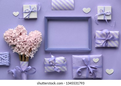 Purple springtime  background with pink hyacinth flowers, wrapped gift boxes and decorative hearts around empty wooden frame with copy-space