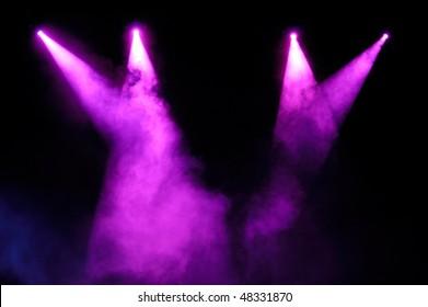 Purple stage spotlights in smoke over black background