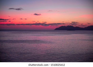 purple sunrise behind a mountain with ocean