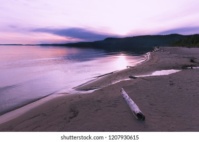 Purple Sunset at Lake Superior. Sandy beach and reflection in water.