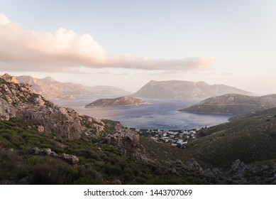 A purple sunset over the Aegean Sea in Kalymnos, Greece surrounded by islands and mountains.