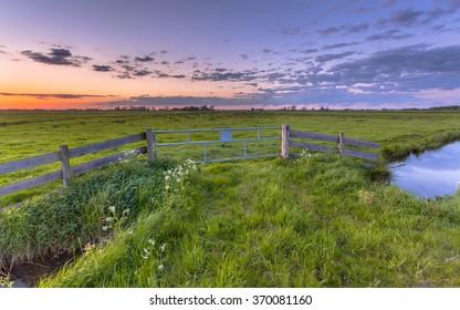 Purple sunset over fence in dutch polder landscape near Groningen