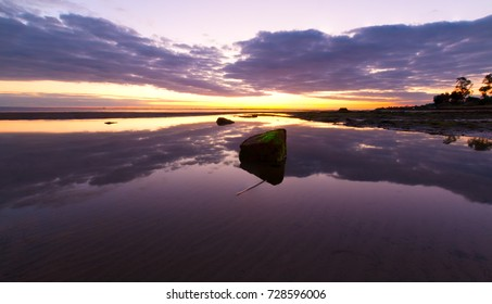 Purple sunset sky over a rock reflecting in the water at the beach