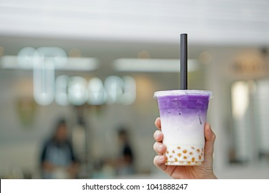 Purple sweet potato milk tea - Hand holding a glass of iced taro latte with boba or golden bubble on blurred background, Most Popular in Taiwan.
