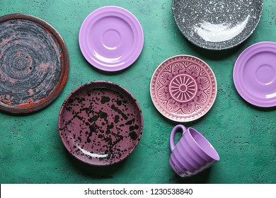 Purple tableware on color background, top view