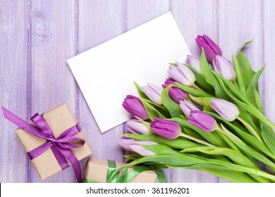 Purple tulip bouquet, blank greeting card and gift boxes. Top view over wooden table