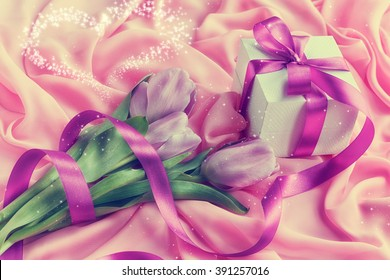 Purple tulip bouquet and gift box on pink textile background with copy space
