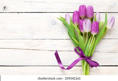 Purple tulip bouquet over wooden table with copy space