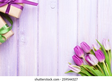 Purple tulips and gift boxes over wooden table. Top view with copy space