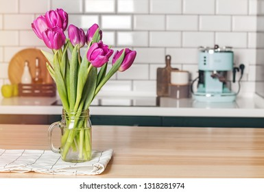 Purple tulips in a glass jar standing on the modern kitchen with white tile