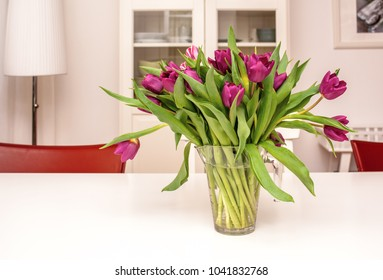 Purple tulips in a glass vase in bright living room