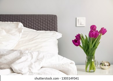 Purple tulips standing on a nightstand in the modern white bedroom near the bed. Spring morning concept.