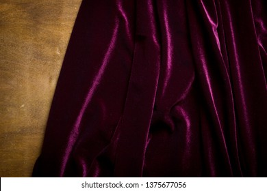 Purple velor fabric on a wooden surface