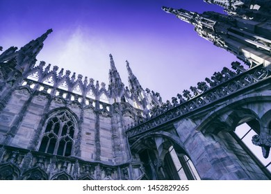 Purple (violet) colored spires and statues on the roof of Duomo Milan Cathedral, Italy over the sky background.
