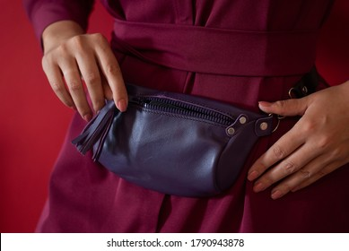 Purple waist bag made from natural leather close-up view on the unrecognizable woman on the green background. Concept of city accessoires and travel. Red color
