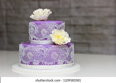 Purple wedding cake with silky white lace and flowers. Very gently looking cake on two floors.