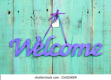 Purple welcome sign with wooden heart hanging on antique weathered green wood door