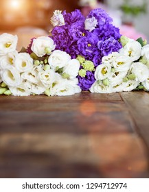 Purple and white contrasting flowers placed on wooden surface.