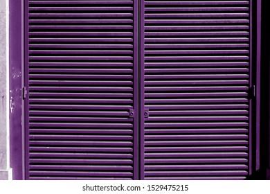 Purple window shutter on the wall.