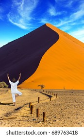 Purple and yellow dune of the Namib desert. An elderly woman practicing yoga in the desert. The concept of extreme and exotic tourism