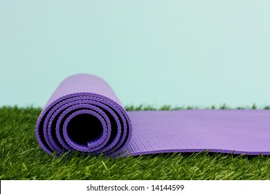 Purple Yoga Exercise Mat On Green Grass