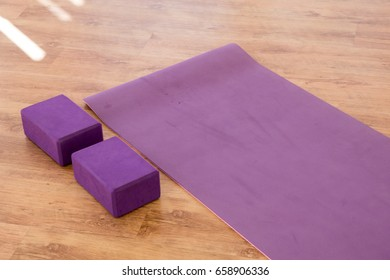 purple yoga mat and purple yoga blocks on a wooden yoga studio floor