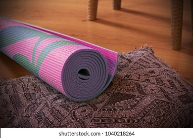 Purple Yoga mat with floral pattern on a natural wooden bench. Textured close up shot of yoga equipment or accessories. Studio or home practice space for meditation.